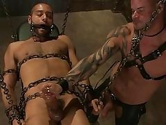 Chained menial gets a handjob